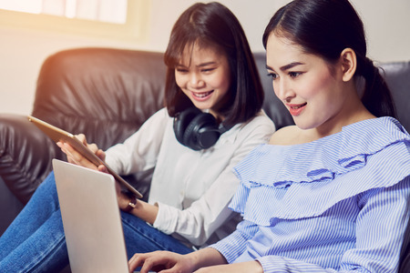 Asian girl in blue casual dress listening to music from black headphones and use laptop. In a comfortable and good mood, In the living room on the sofa.