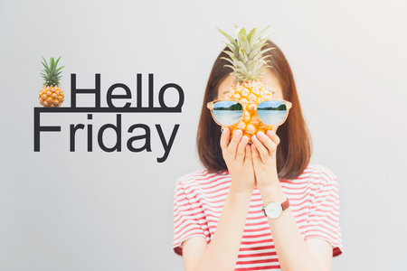 Young girl in red dress and hold pineapple in hand, Wear sunglasses with a reflection of the beach and island. And have a message Hello Friday. Concept summer travel. Stock Photo