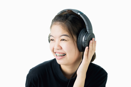Asian girl in black casual dress listening to music from black headphones. In a comfortable and good mood, on a white background gives a soft light.