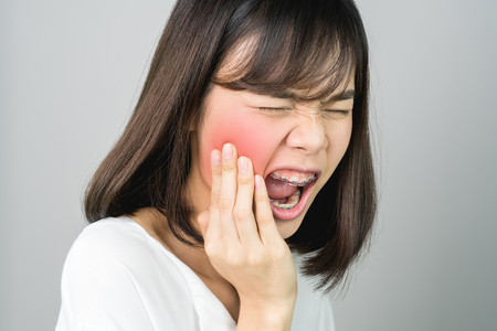 Asian girl in white casual dress Show off the toothache, Maybe because of not maintaining good oral health. on a gray background gives a soft light.