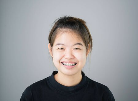 portrait of smiling asian young women put on the braces. on a gray background gives a soft light.