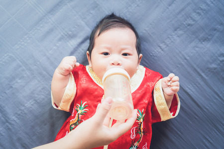 Baby in red dress on blue cloth and eating milk. Concept Chinese New Year.