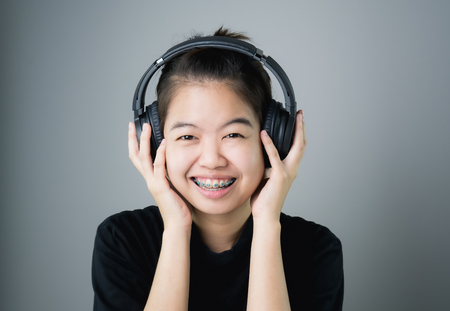 Asian girl in black casual dress listening to music from black headphones. In a comfortable and good mood, on a gray background gives a soft light.