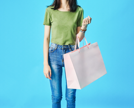 Woman wearing green shirts holding shopping bags in the blue background. Stock Photo