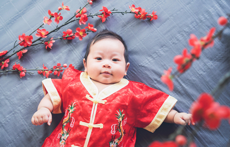 Baby in red dress on blue cloth with flower and looking. Concept Chinese New Year.