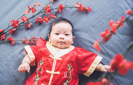꽃과 찾고 파란 옷감에 빨간 드레스에 아기. 개념 구정.