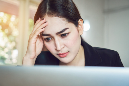 Business women sit and strain the computer screen for a long time. Because the work has been overloaded. Stock Photo