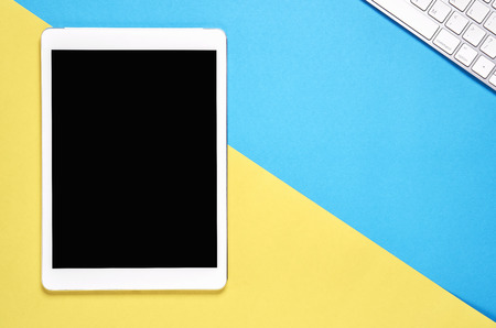 Top view, Modern workplace with tablet placed on a pastel yellow background. Copy space suitable for use in graphics.