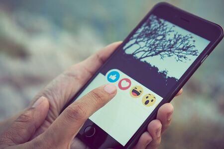 Bangkok, Thailandia - 12 marzo 2018: la mano delle donne sta premendo lo schermo di Facebook su Apple iphone 6 sul prato, i social media stanno usando per la condivisione di informazioni e il networking.