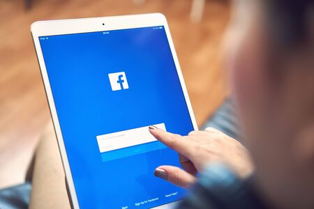 Bangkok, Thailand - January 3, 2018 : hand is pressing the Facebook screen on apple ipad pro,Social media are using for information sharing and networking. Standard-Bild - 136695088