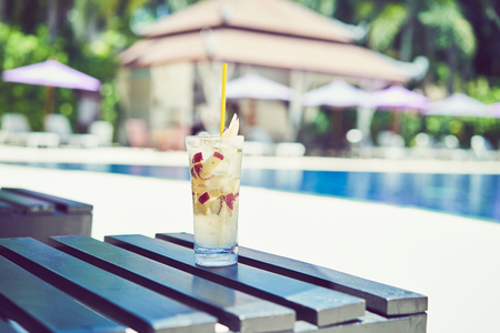 A glass of water juice on swimming pool in vacation and summer time.