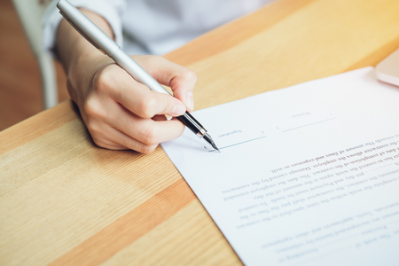 closeup of signing a documentation agreement and pen on the table. Stock Photo