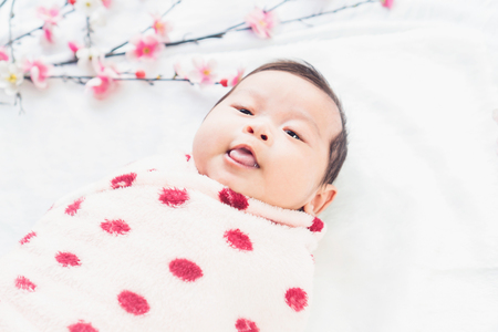 Cute little baby lies on a white cloth and wrapped in quilt, Looking around. on white background. Stock Photo