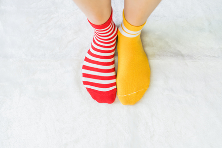 Legs in socks two colors alternate, Red and yellow side stand on white fabric floor.
