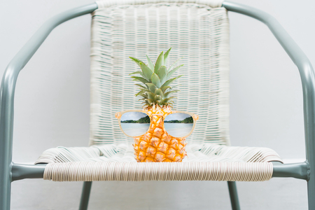 Pineapple with glasses is worn is placed on the table. Summer concept.