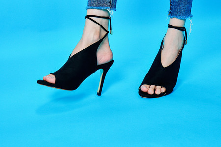 Legs of women wearing high heels, black fashion beautifully. Standing on a blue background