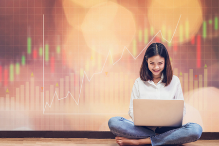 Woman sitting using laptop and show trading graph with the stock exchange trading graph for background. concept financial and forex. Stock Photo