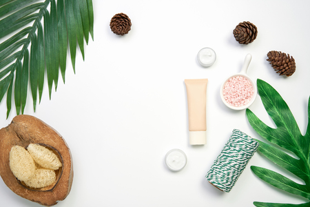 Mockup of cosmetic cream bottle, Blank label package and ingredients on a green leaves background. Concept of natural beauty products. Stock Photo