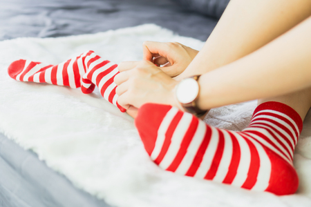 The girl sit on a white carpet and put on socks, white punctuate red side.