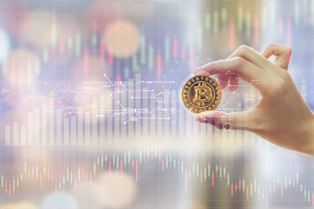 Hand of woman holding a Gold Bitcoin is digital currency, and show graph with the stock exchange trading graph for background. concept financial and forex.