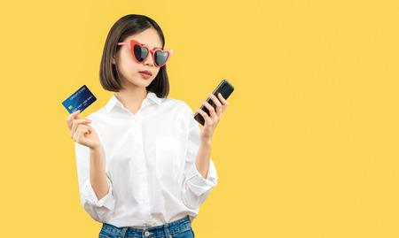 オンラインショッピングでスマートフォンとクレジットカードを持っている幸せな笑顔の女性。広告を入れるためのスペースをコピーします。