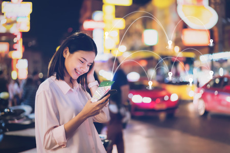 Women use smartphone at night on city shopping street, and use the map application in  navigation.