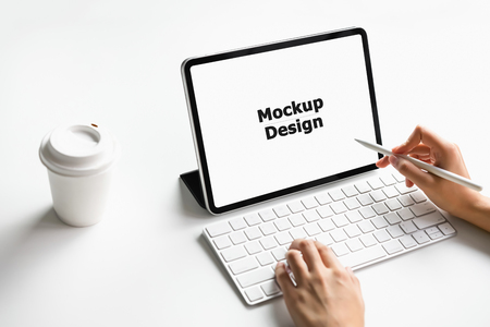 Woman typing keyboard laptop and tablet screen blank on the table mock up to promote your products. Concept of future and trend internet for easy access to information.