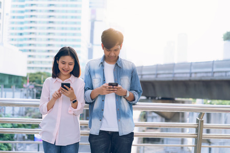 Young people are using smartphone and smiling while sitting on free time. technology concept