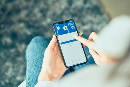 Bangkok, Thailand - July 30, 2019 : woman hand holding and is pressing the Facebook screen on apple smart phone ,Social media are using for information sharing and networking. Editorial