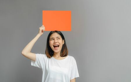 Asian woman of happy smiling holding a blank orange poster on gray background. with empty space for text. Reklamní fotografie