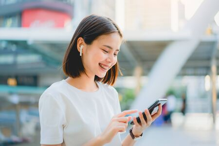 Asian women of happy smiling are listening to music from white headphones. And using hands touch to use various functions, happy mood.