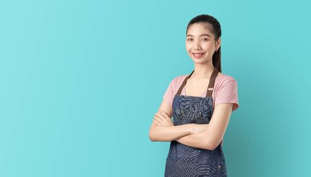 Small business, Asian woman in apron and standing with crossed arms against and looking forward on blue background. Stock Photo
