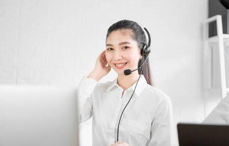Schöne asiatische Beraterin mit Mikrofon-Headset des Kundensupport-Telefonbetreibers am Arbeitsplatz.