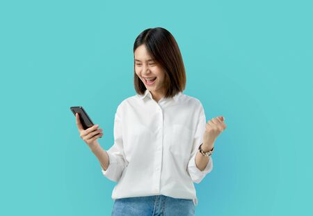 Young smiling Asian woman holding smart phone with fist hand and excited for success on light blue background.