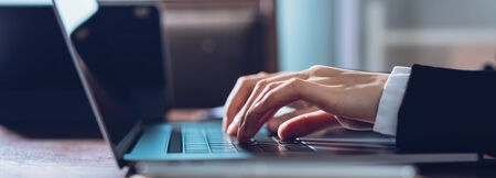 Close up of business woman hands typing on laptop computer and searching web, browsing in the workplace at office. proportion of the banner for advertisement.