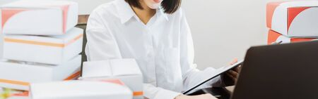 Beautiful smiling woman braces using laptop computer checking order for customer and online delivery for ready packaging. proportion of the banner. Stock Photo