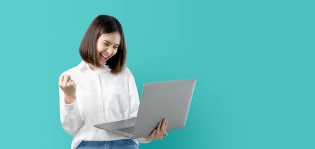 Young Asian woman smiling holding laptop computer with fist hand and excited for success on light blue background. Stock Photo