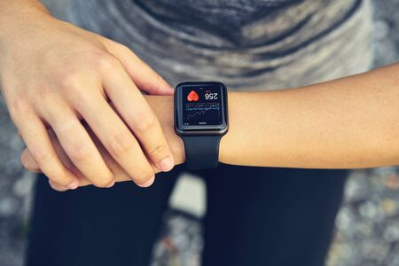 Young woman checking the sports watch measuring heart rate and performance after running. Standard-Bild - 128423907