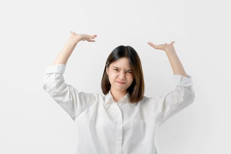 Young Asian woman in white casual clothes attempt to hold something heavy from above.