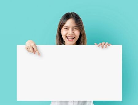 Young Asian woman holding blank paper with smiling face and looking on the blue background. for advertising signs. Stock Photo