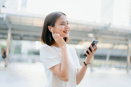 Women are listening to music from white headphones. And using hands touch to use various functions, happy mood.