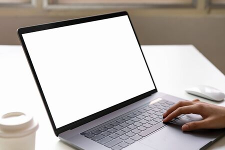 Woman using laptop on the table, mock up of blank screen.