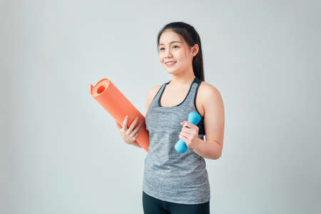 Smiley Asian woman wearing sportswear holding orange mat with blue dumbbell in living room. Healthy lifestyle concept.