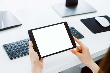 Woman holding digital tablet mockup of blank screen and computer on the table office. Take your screen to put on advertising.