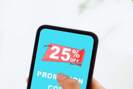 Woman holding smartphone to enter the code to get a discount from the store. Concept of providing marketing services on internet for easy access to information.
