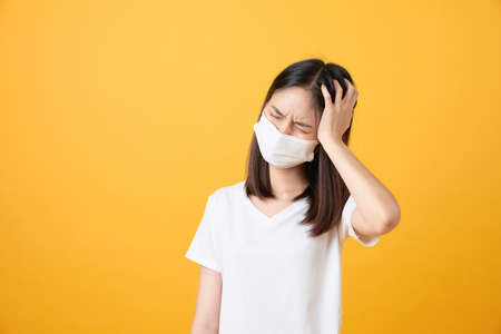 Asian women wear masks to protect disease and the headache from a virus on orange background.
