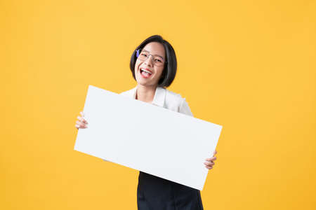 Young Asian woman holding blank paper with smiling face and looking on the orange background. for advertising signs. Stock Photo