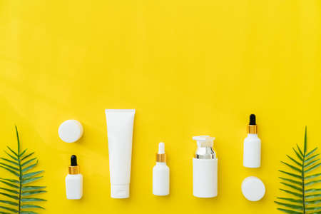 White bottle cream, mockup of beauty product brand. Top view on the yellow background. Stock Photo