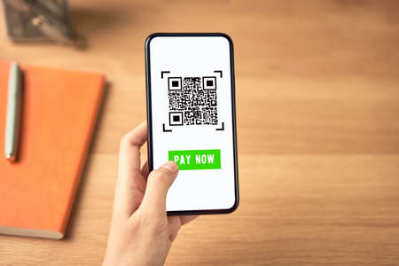 Woman using smartphone for qr code payment mobile banking on application wallet.