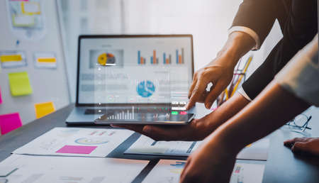 Stock exchange market concept, businessman trader holding tablet with graphs analysis candle line on table in office, diagrams on screen.